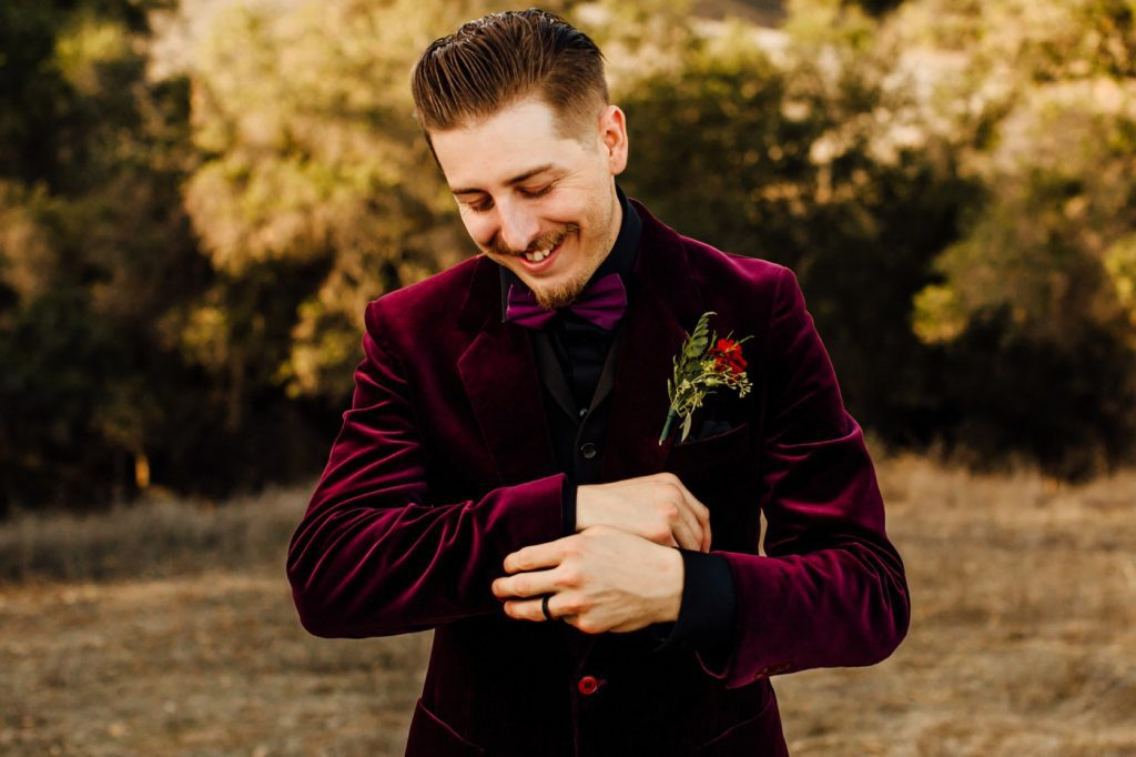 Groom in burgundy velvet suit jacket