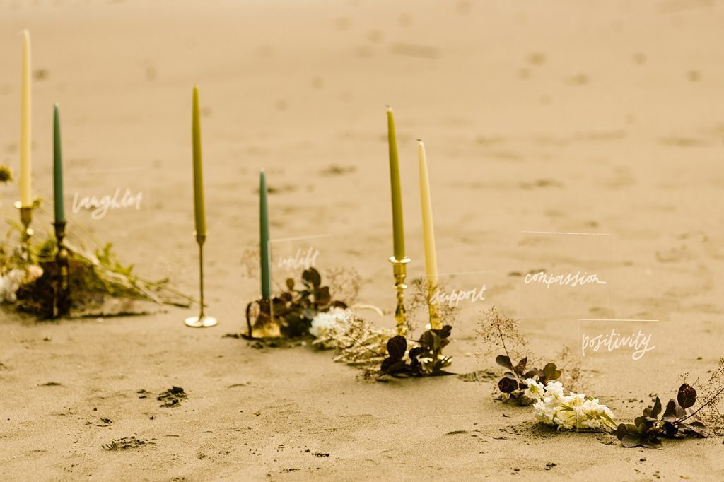 Candles and floral ceremony set up on the beach elopement