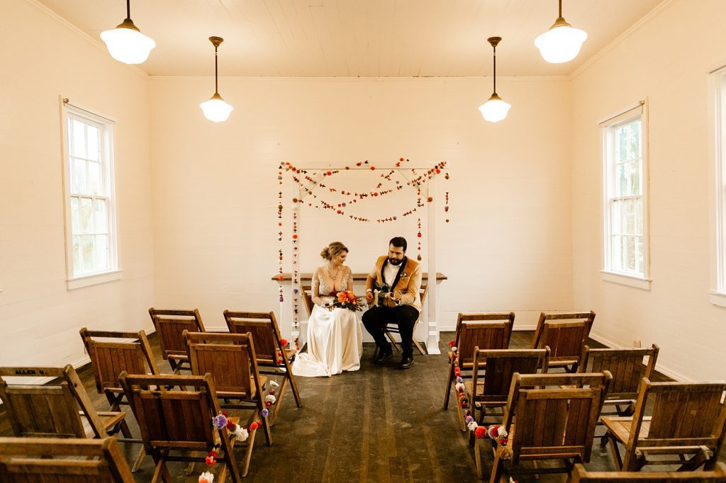 Unique wedding ceremony ideas, groom playing guitar to bride, Christiansons Nursery Wedding Photographer Schoolhouse