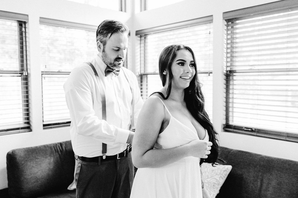 black and white photo couple getting ready together groom zipping up dress