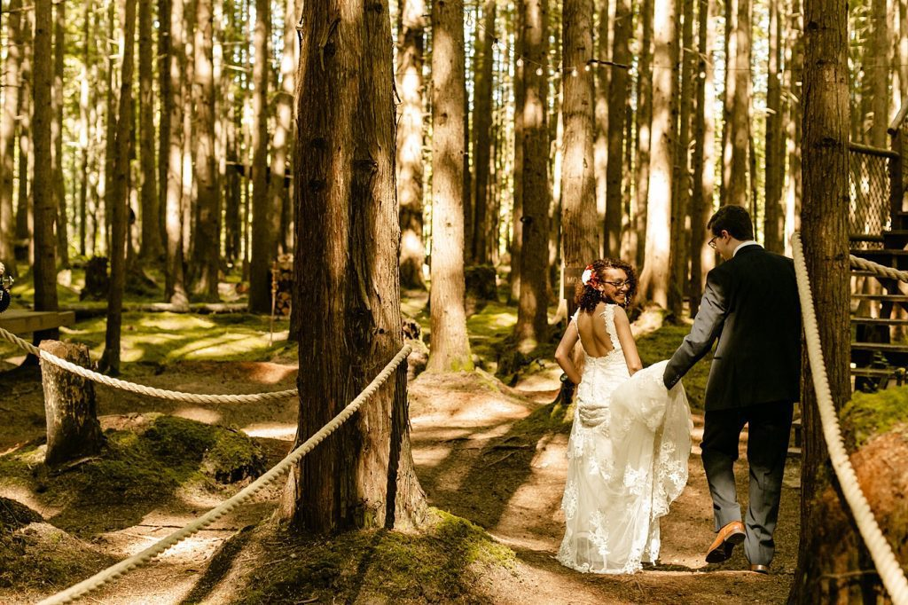 emerald forest wedding venue photographer tminspired photography seattle washington groom holds brides dress walking down aisle in the forest secluded sun kissed lighting