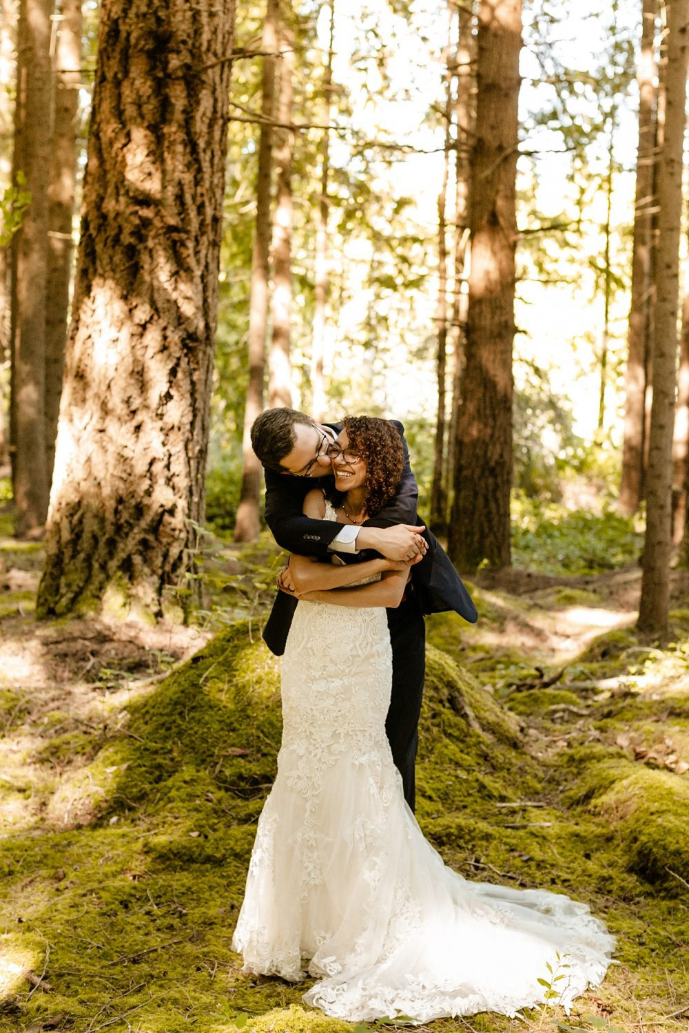 best wedding photographer in seattle washington, emerald forest elopement venue, How To Choose The Best Wedding Vendors, groom hugging bride from behind in the middle of the sun kissed forest