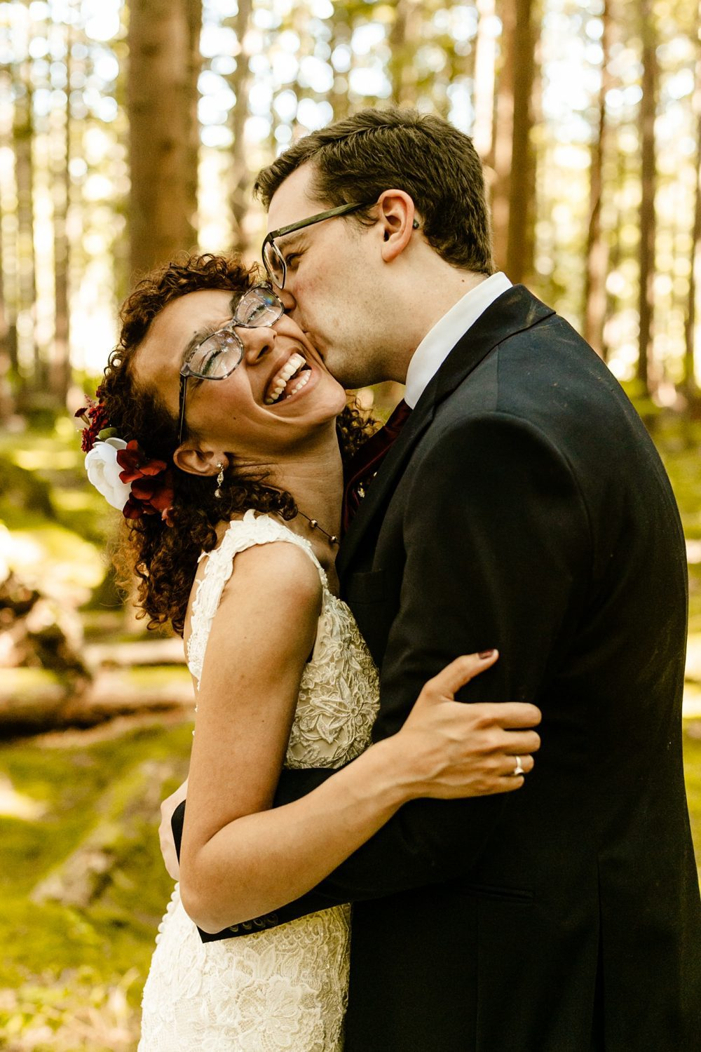How To Choose The Best Wedding Vendors, married couple elopement kissing on cheek, Black bride hair and makeup, warm tones photographer, emerald forest wedding venue