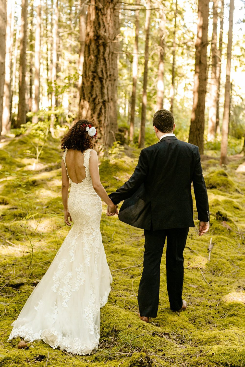 How To Choose The Best Wedding Vendors emerald forest wedding venue photographer bride and groom walking together on moss covered ground in the woods