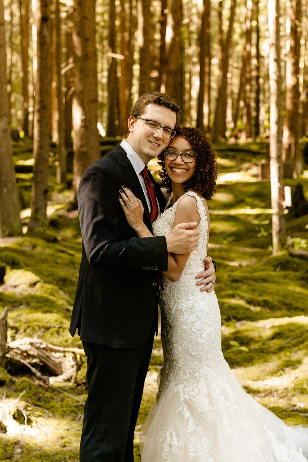 bride and groom pose smiling at the camera, grooms hand on brides arm, Black bride, lace dress, red tie groom, forest venue in Washington