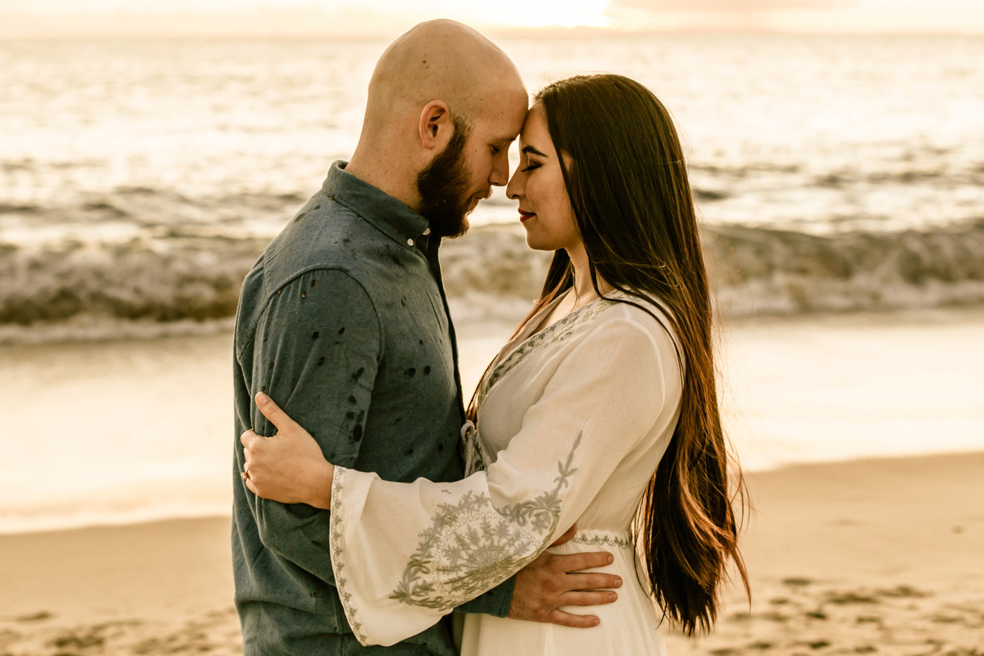 engagement session couple hugging on beach