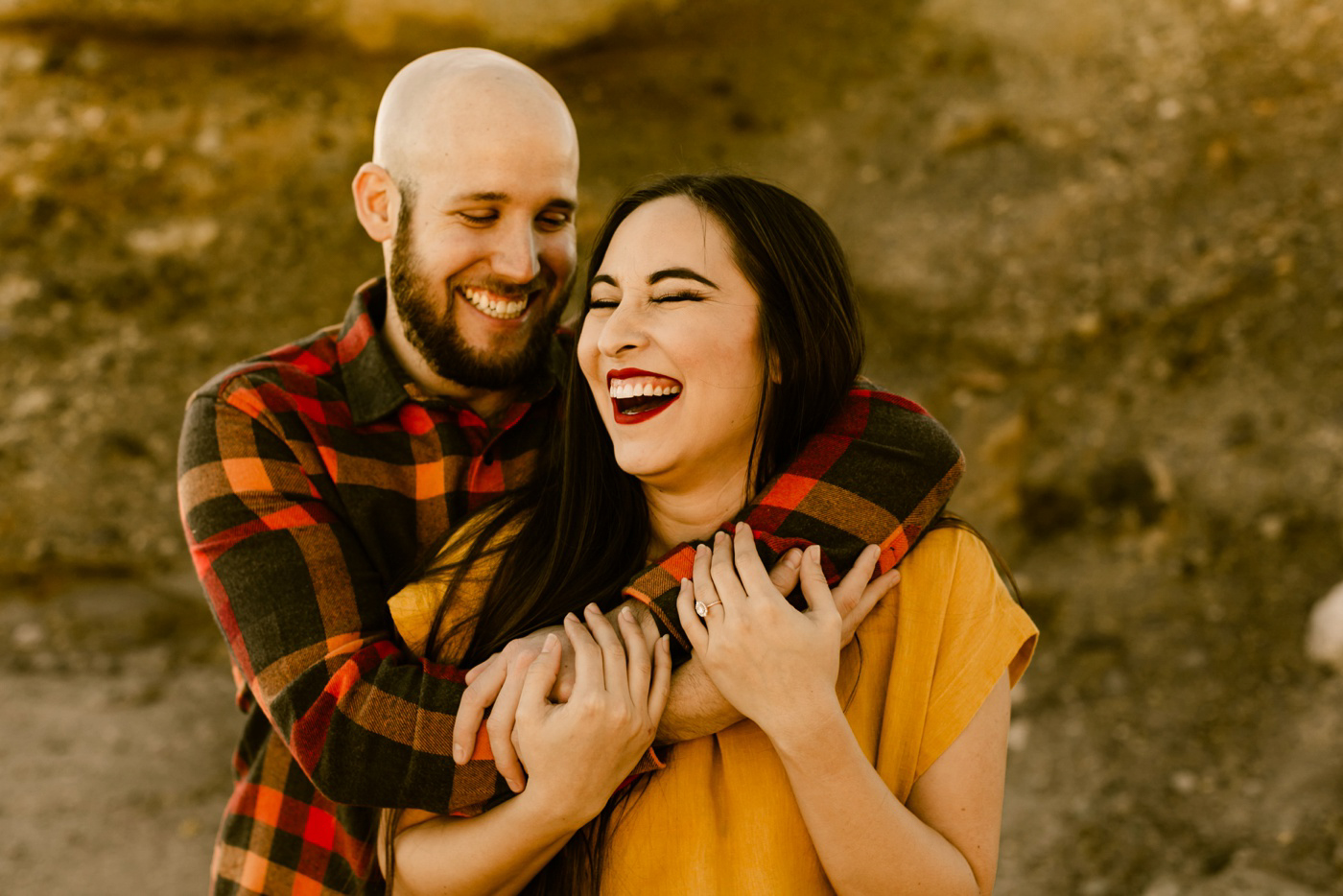 couple laughing together while taking engagement photos