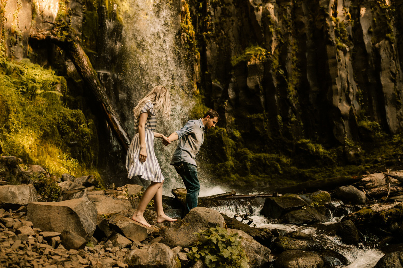 couple near waterfall in the PNW taking engagement photos
