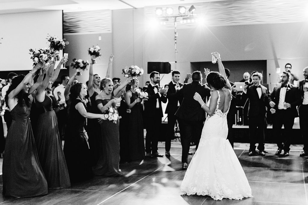 Candid grand entrance with bridal party on the dance floor, wedding photographer