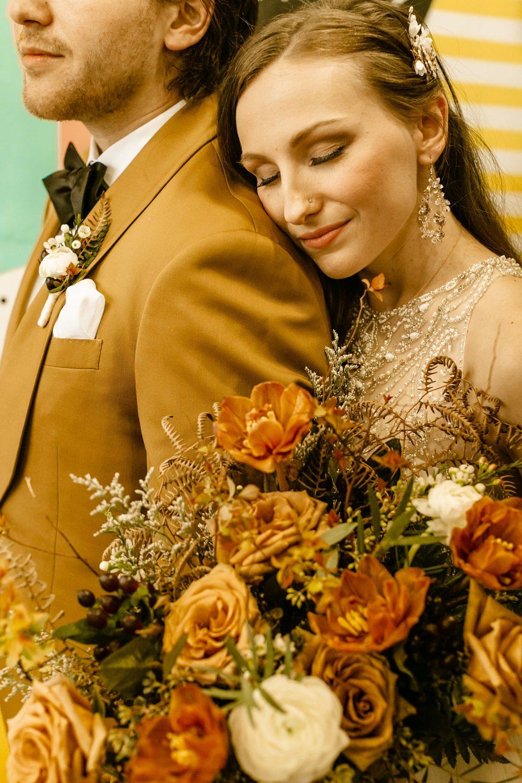 Portland coffee shop elopement photographer, neutral tone bouquet, groom gold suit jacket