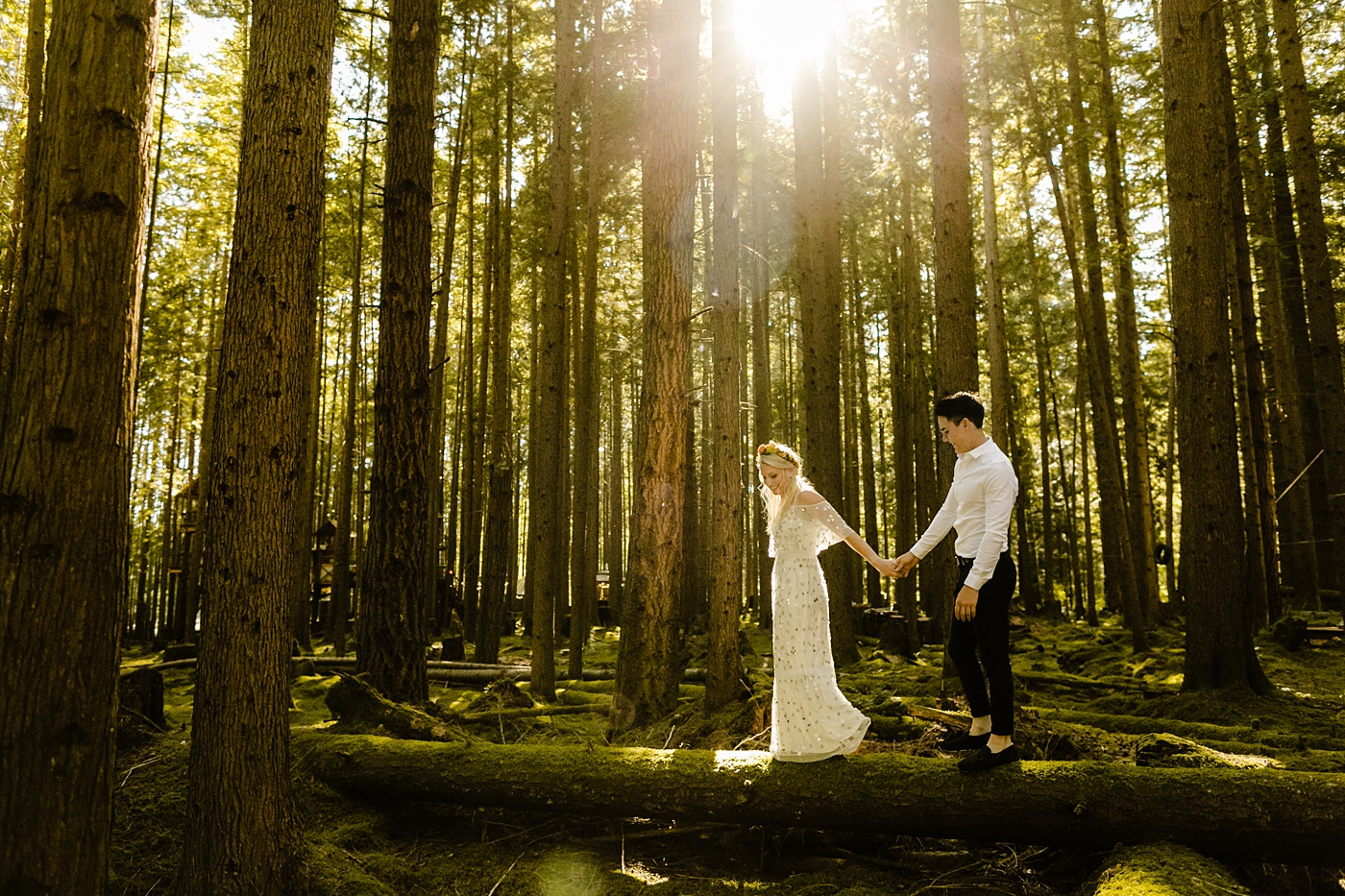 couple walking along a moss covered log in the forest, elopement location