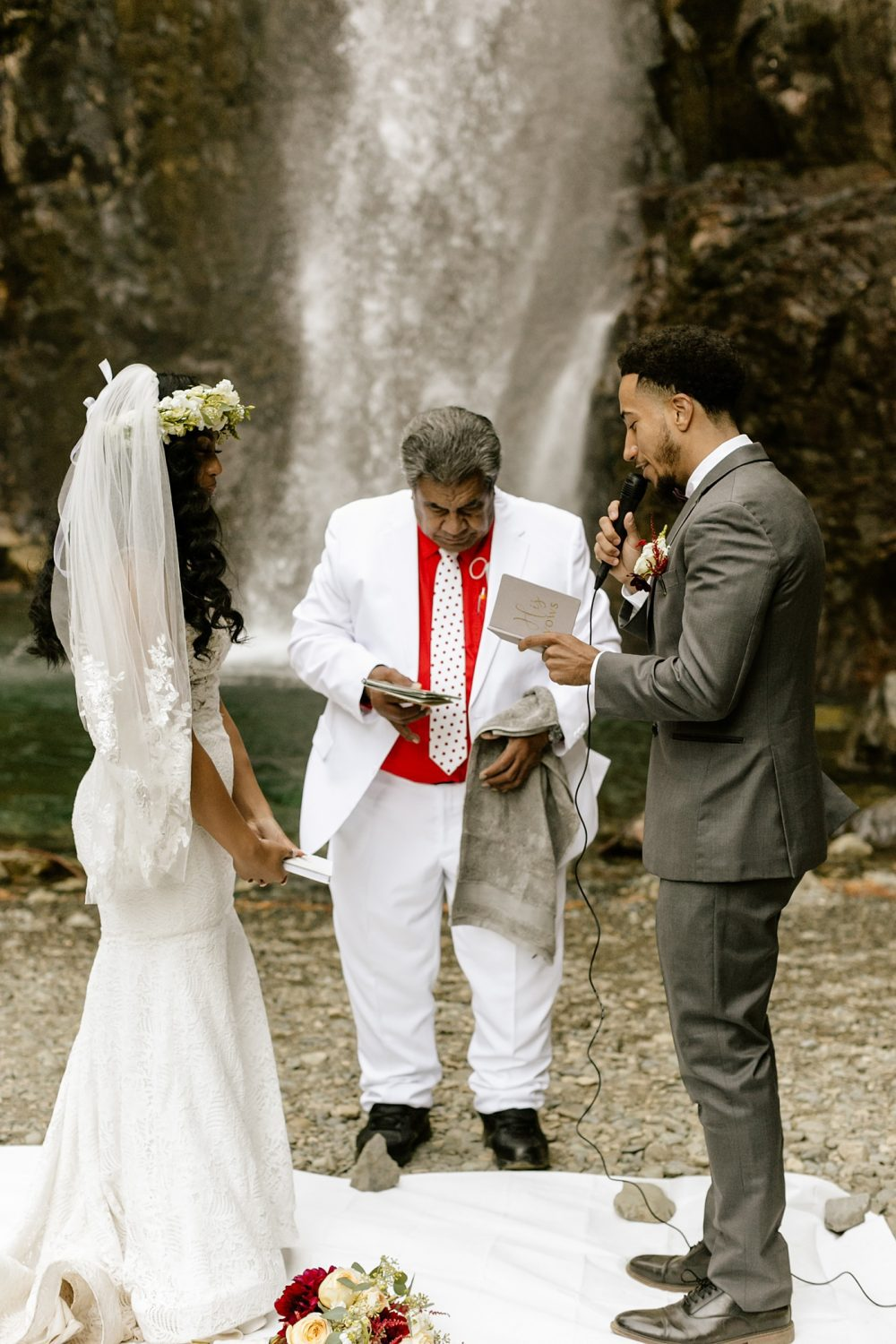 groom reading vows to bride at the base of a waterfall ceremony