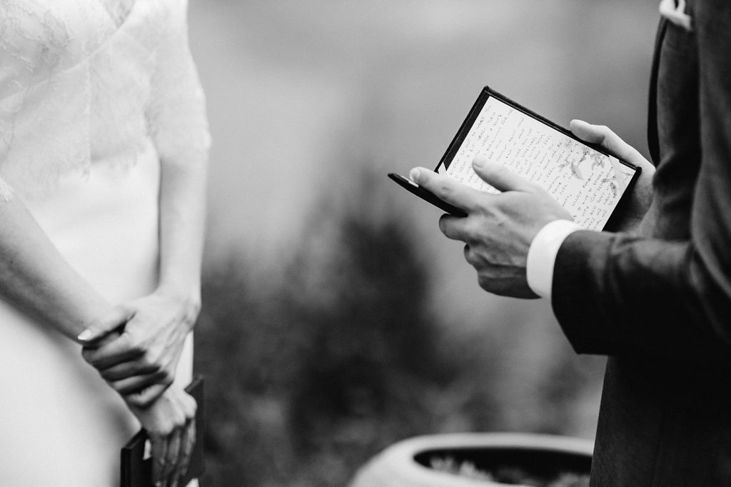 groom reading personal vows in vow book black and white photo