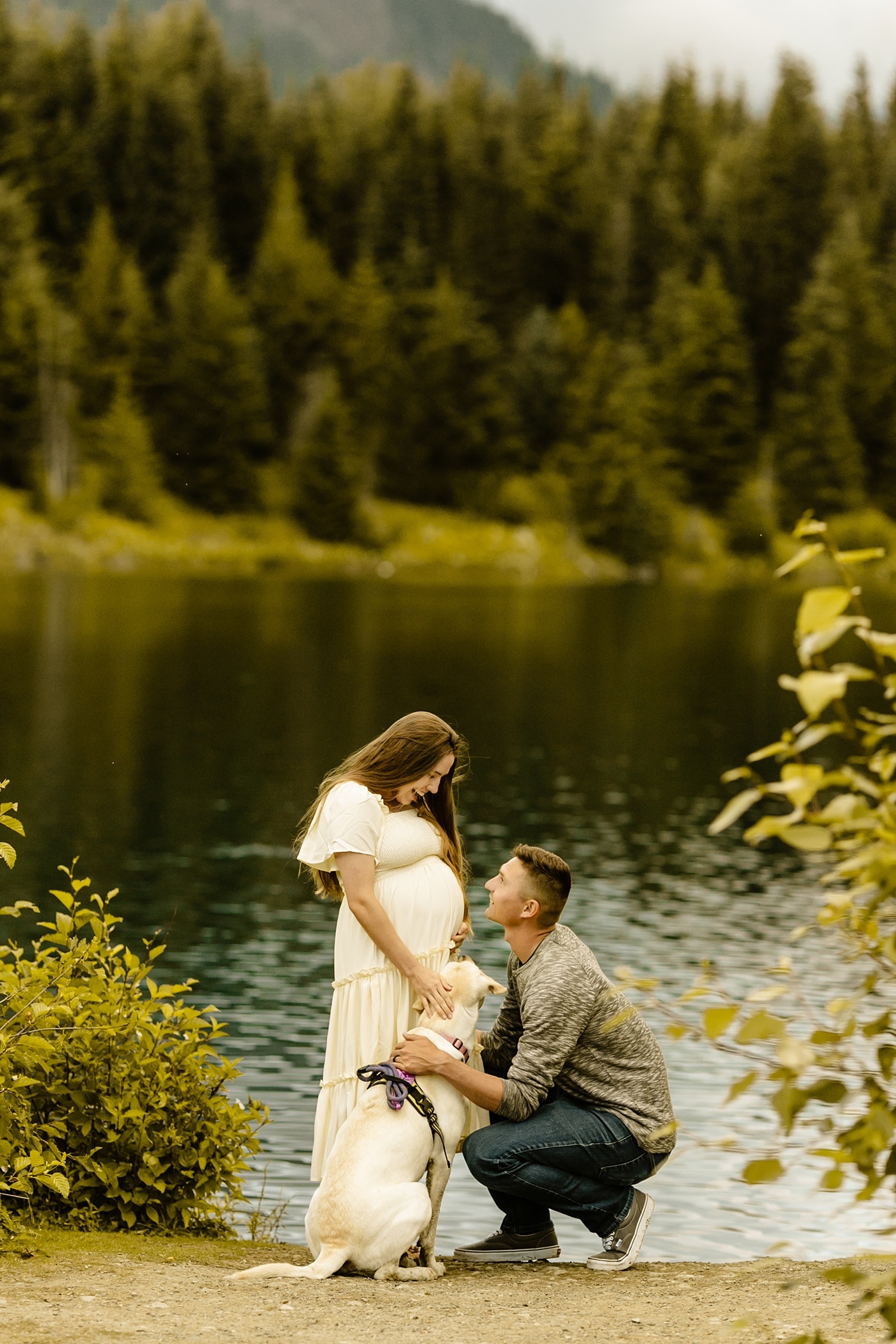 husband kneeling and kissing pregnant wife